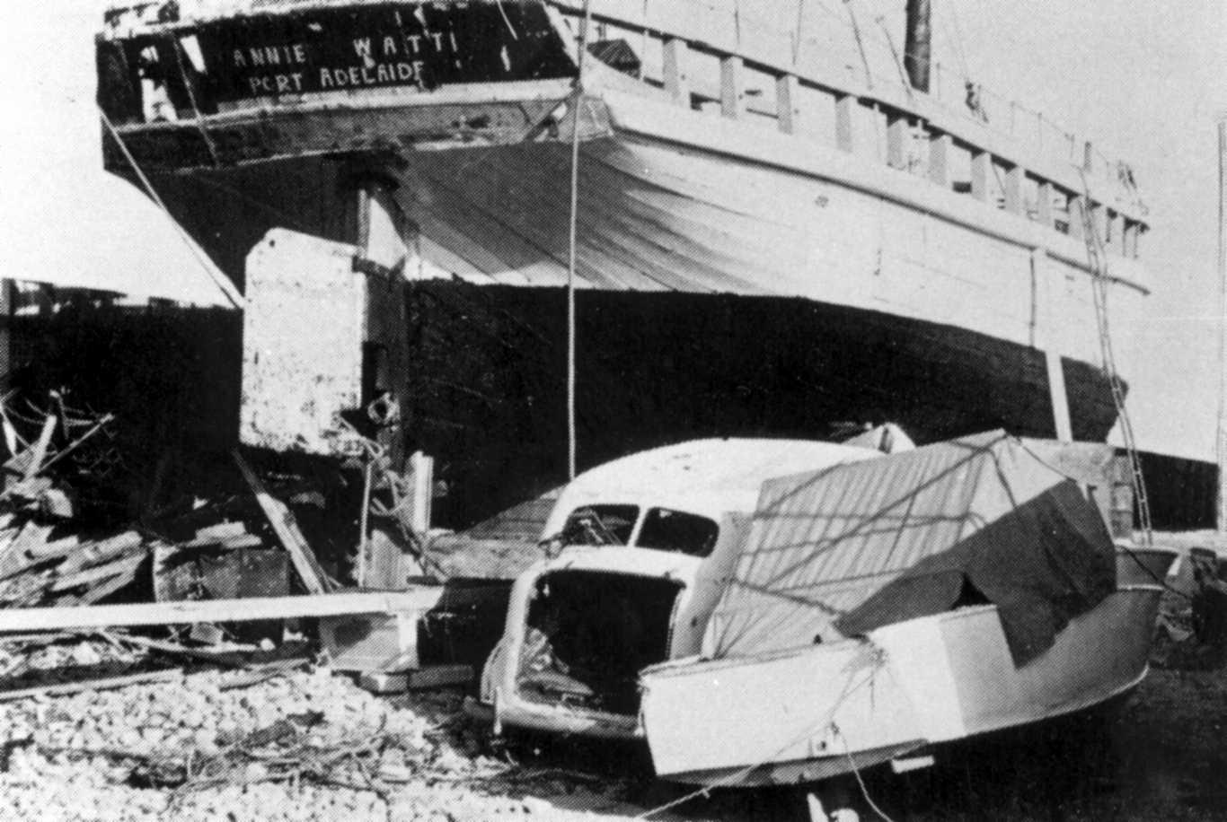 This image shows vessel on land from rear angle, showing rudder, and has an old car in foreground.