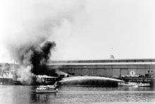 1942 Police Launch at Port Adelaide with fire on vessel in the background being extinguished by fireboat