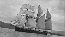 Image: three masted topsail schooner on water, sails fully unfurled